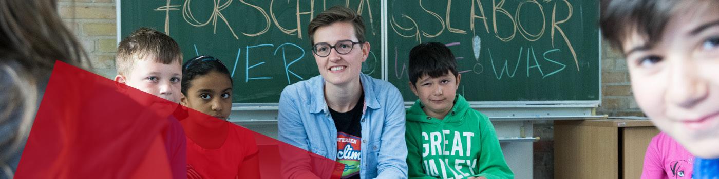 Fellow mit Schülern vor einer Schultafel mit der Aufschrift »Forschungslabor«